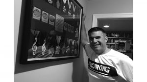 Jason Herman standing in front of large display case of medals