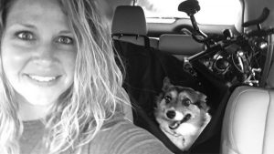 Myranda and her dog in her car in a selfie. She's on the way to a race. You can see the bike in the back of the car.